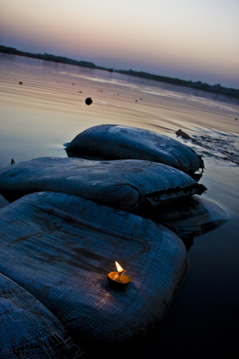 Diya at Kesi Ghat by Udit Kulshrestha, Image Photography, Digital Print on Archival Paper, Blue color
